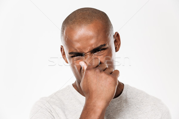 Young african man closes a nose from a stench. Stock photo © deandrobot
