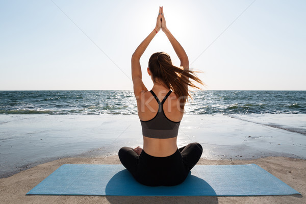Back view of healthy young sport woman practicing yoga sitting i Stock photo © deandrobot