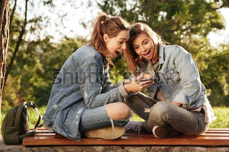 Two young pretty woman whispering secrets while sitting on woode Stock photo © deandrobot
