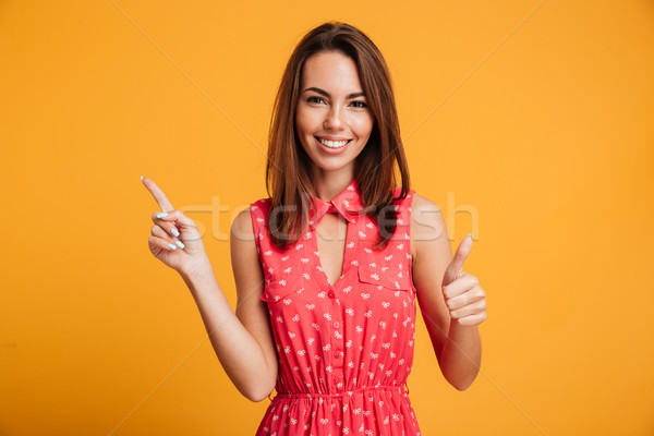 Smiling brunette woman in dress pointing up Stock photo © deandrobot