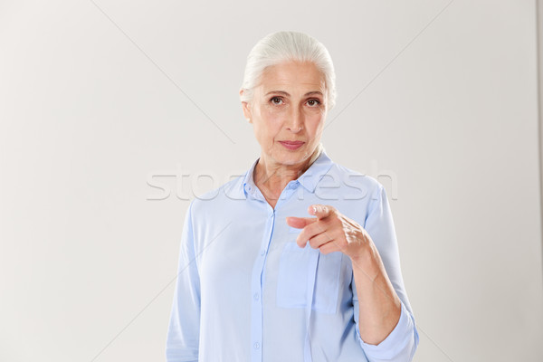 Portrait of playful elderly woman pointing with finger to you Stock photo © deandrobot