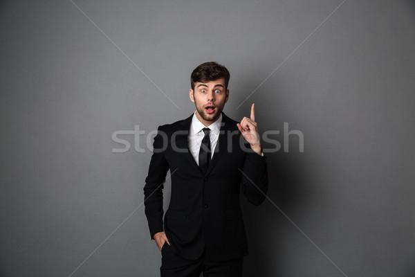 Maravilhado moço terno indicação dedo olhando Foto stock © deandrobot