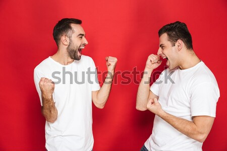 Strong young man showing biceps Stock photo © deandrobot