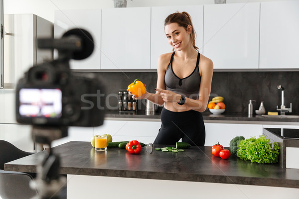 Smiling healthy young girl recording her blog episode Stock photo © deandrobot