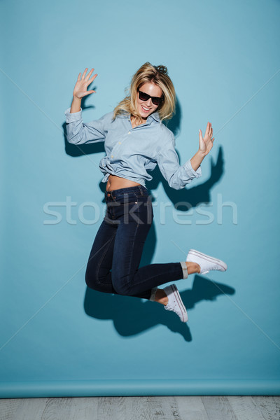 Full length image of Pleased blonde woman in shirt and sunglasses Stock photo © deandrobot