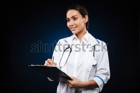 Positive young woman doctor writing in folder and looking aside Stock photo © deandrobot