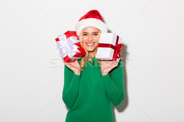 Portrait of a cheerful girl dressed in christmas hat Stock photo © deandrobot