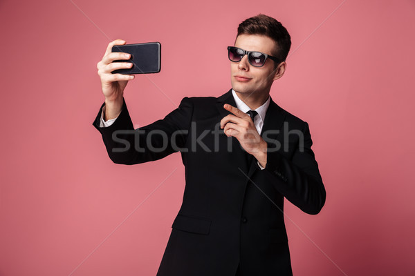 Concentrated young businessman make selfie by mobile phone. Stock photo © deandrobot