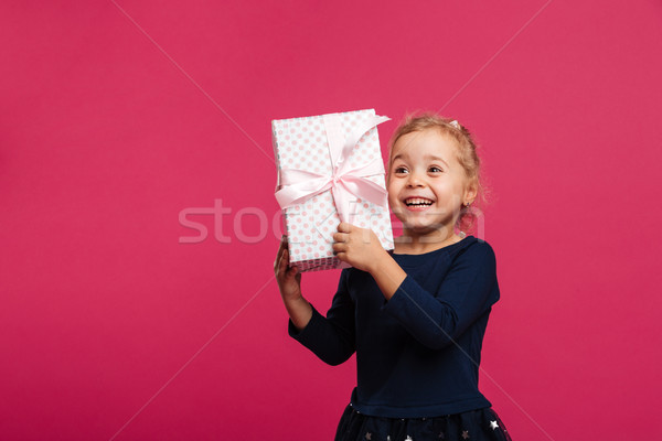 Happy young blonde girl holding gift box and rejoices Stock photo © deandrobot