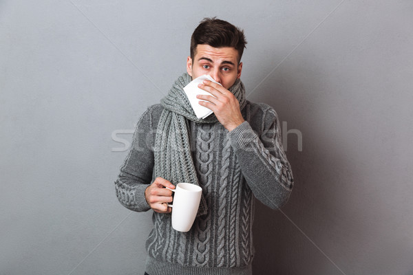 Sick Man in sweater and scarf having runny nose Stock photo © deandrobot