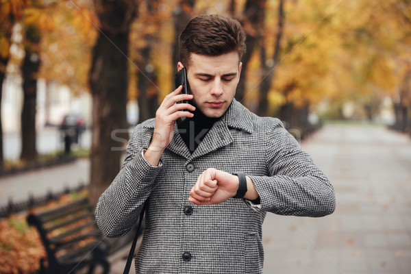 Picture of businesslike man speaking on mobile phone while going Stock photo © deandrobot
