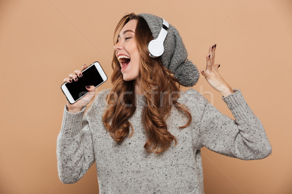 Portrait of emotional young woman in gray woolen hat holding her Stock photo © deandrobot