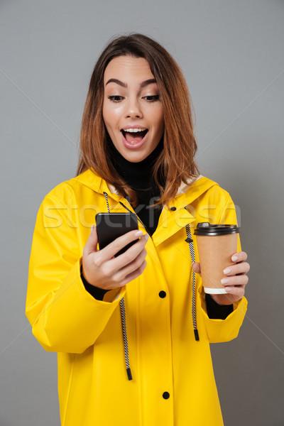 Portré izgatott lány esőkabát néz mobiltelefon Stock fotó © deandrobot