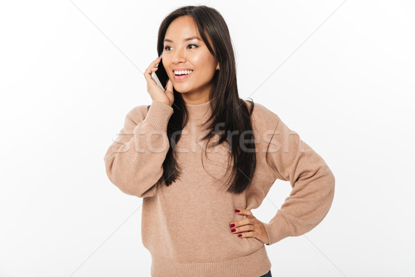 Cheerful woman talking by mobile phone. Looking aside. Stock photo © deandrobot