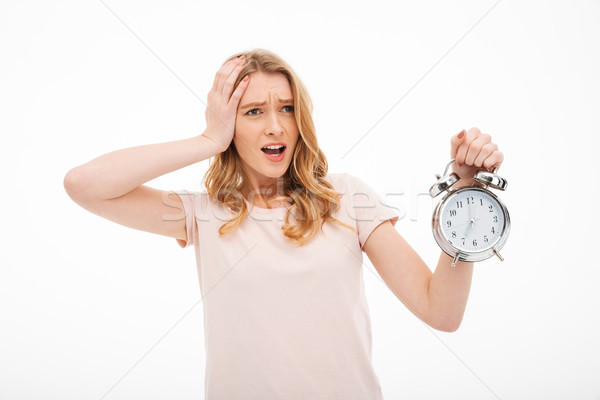 Screaming young confused woman holding alarm clock. Stock photo © deandrobot