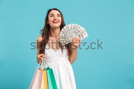 Portrait of excited female shopaholic standing with lots of pack Stock photo © deandrobot