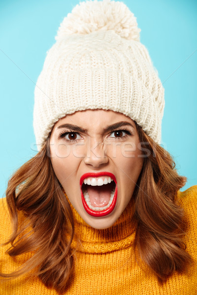 Close up portrait of an angry furious girl in winter hat Stock photo © deandrobot