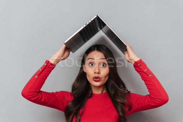 Shocked brunette woman in red blouse holding laptop computer overhead Stock photo © deandrobot