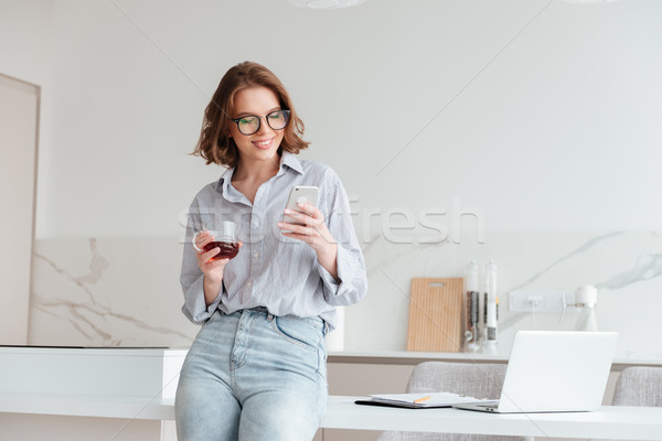 Portrait of a happy attractive woman using mobile phone Stock photo © deandrobot