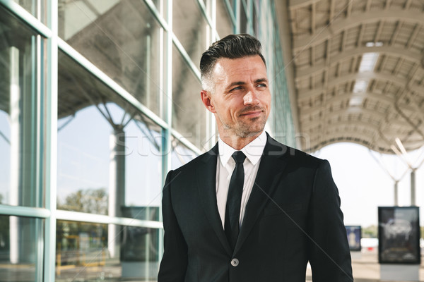 Smiling businessman dressed in suit walking outside airport Stock photo © deandrobot