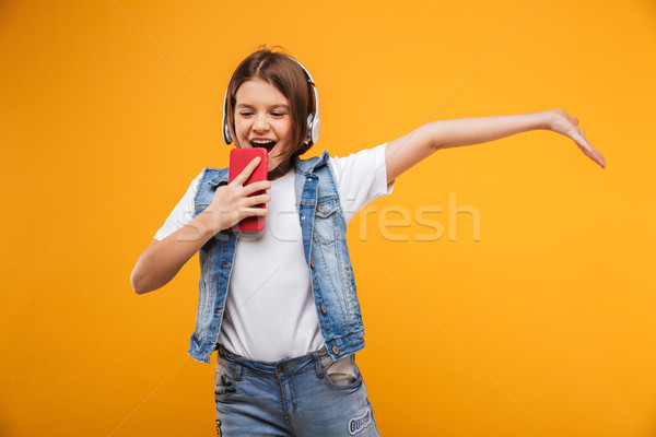 Portrait of a happy little schoolgirl listening to music Stock photo © deandrobot