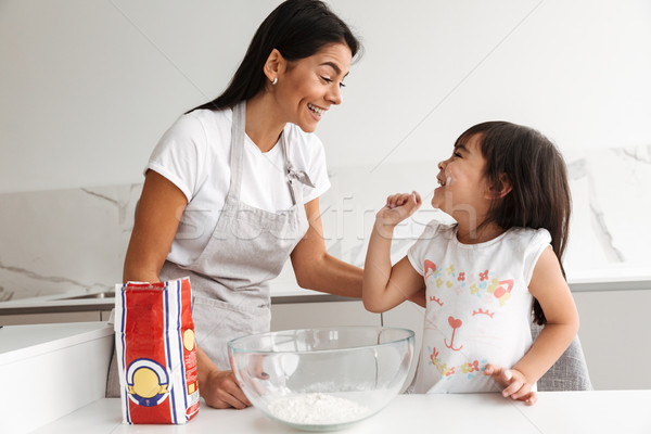 Young mother in apron cooking and baking with her smiling little Stock photo © deandrobot