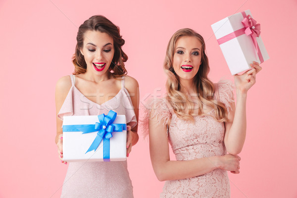 Stock photo: Two surprised women in dresses holding gift boxes and rejoices