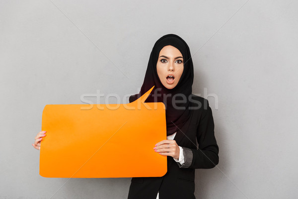 Portrait of muslim excited woman 20s in black hijab looking at c Stock photo © deandrobot