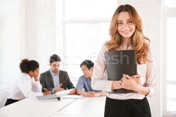 Smiling young woman holding folder Stock photo © deandrobot