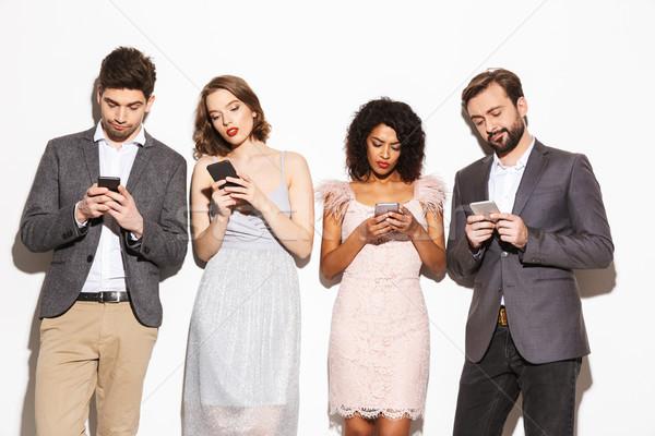 Csoport modern jólöltözött emberek mobiltelefonok izolált Stock fotó © deandrobot
