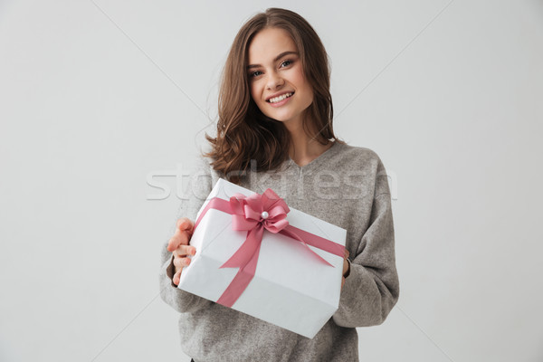 Happy brunette woman in sweater holding gift box Stock photo © deandrobot