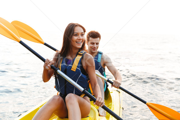 Beautiful young couple kayaking on lake together Stock photo © deandrobot