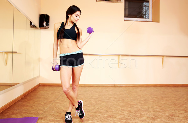 Young fit woman doing exercises with dumbells at gym Stock photo © deandrobot