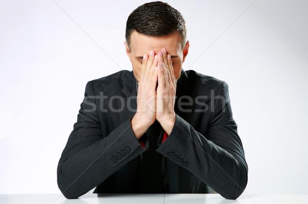 Biznesmen posiedzenia tabeli ręce twarz Zdjęcia stock © deandrobot