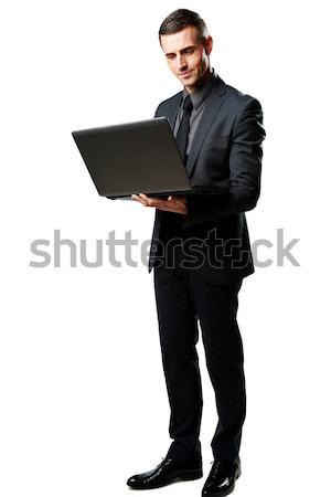 Foto d'archivio: Ritratto · imprenditore · piedi · utilizzando · il · computer · portatile · isolato · bianco