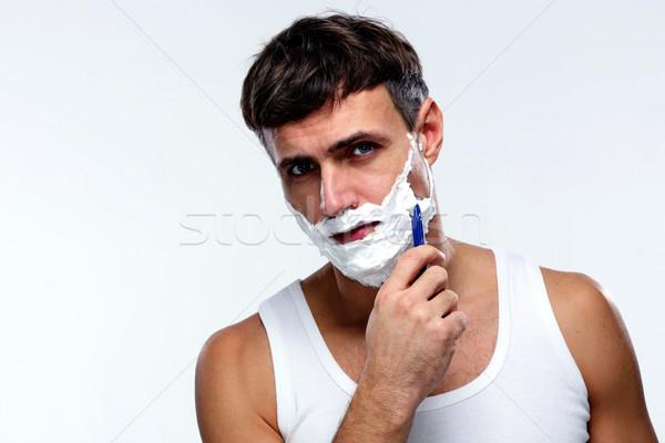 Handsome man shaving over gray background Stock photo © deandrobot