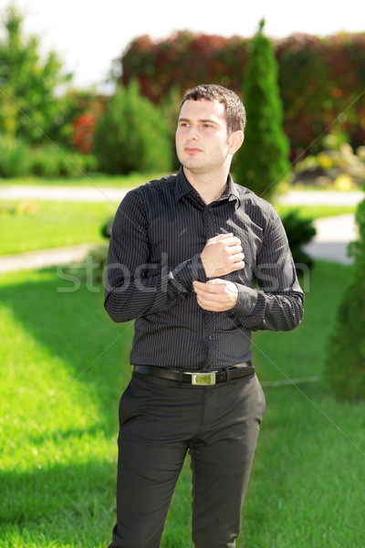 Portrait of young attractive business man standing in the yard in front of his house. Sunny day.  Stock photo © deandrobot