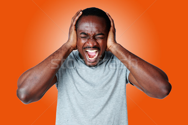 Portrait of african man shouting and closing ear by his hands on orange background Stock photo © deandrobot