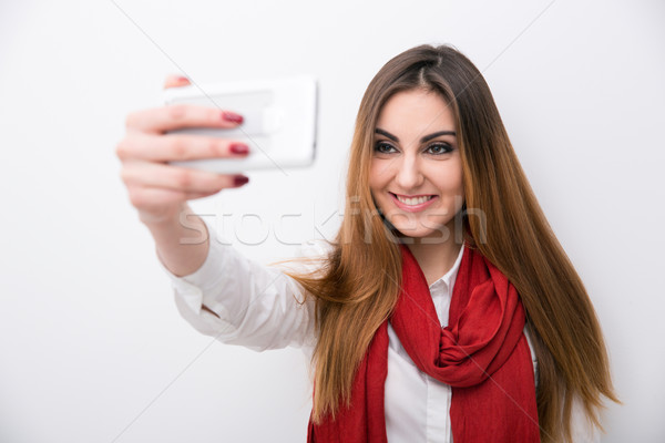 Smiling woman making photo on smartphone Stock photo © deandrobot