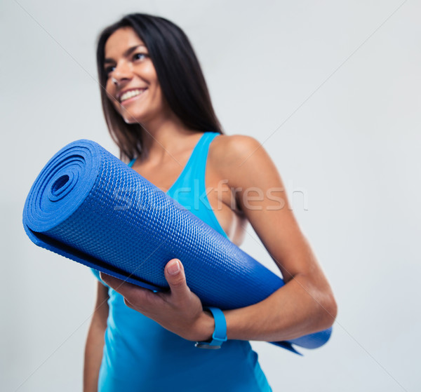 Fitness woman holding yoga mat Stock photo © deandrobot