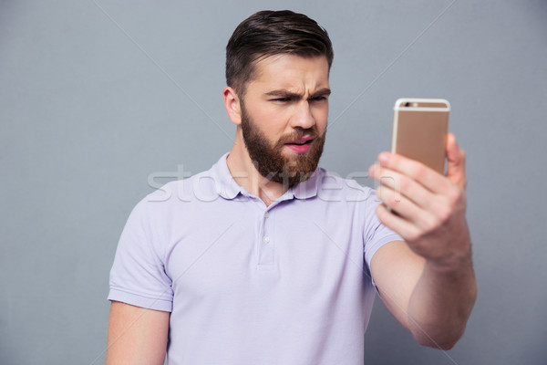 Man looking on smartphone in confusion  Stock photo © deandrobot