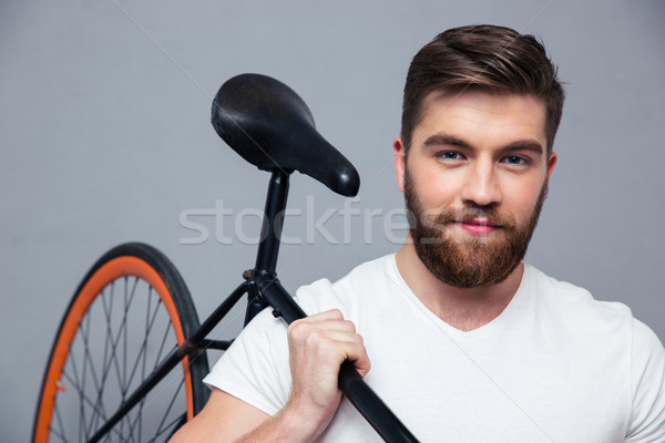 Happy man holding bicycle on the shouder Stock photo © deandrobot