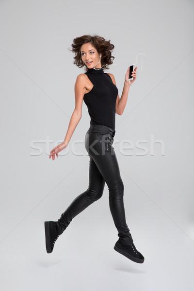 Boldog fürtös gondtalan lány ugrás hallgat Stock fotó © deandrobot