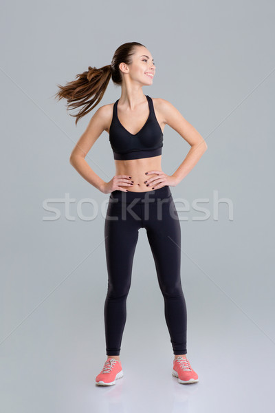 Happy beautiful fitness girl warming up her neck  Stock photo © deandrobot