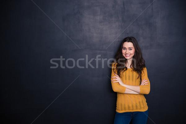 Sonriendo casual mujer pie armas doblado Foto stock © deandrobot