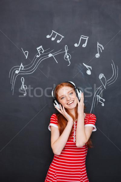 Сток-фото: счастливым · женщину · наушники · доске · привлекательный