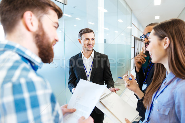 Souriant gens d'affaires permanent parler chef d'équipe groupe Photo stock © deandrobot