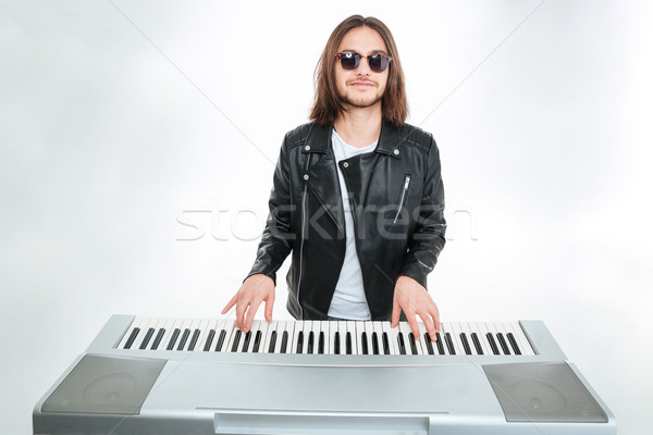 Smiling man with long hair in sunglasses playing on synthesizer Stock photo © deandrobot