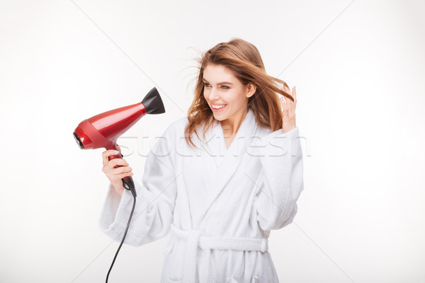 Cheeful lovely young woman drying her hair with dryer Stock photo © deandrobot