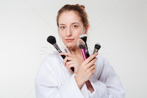 Beautiful woman holding makeup brushes Stock photo © deandrobot